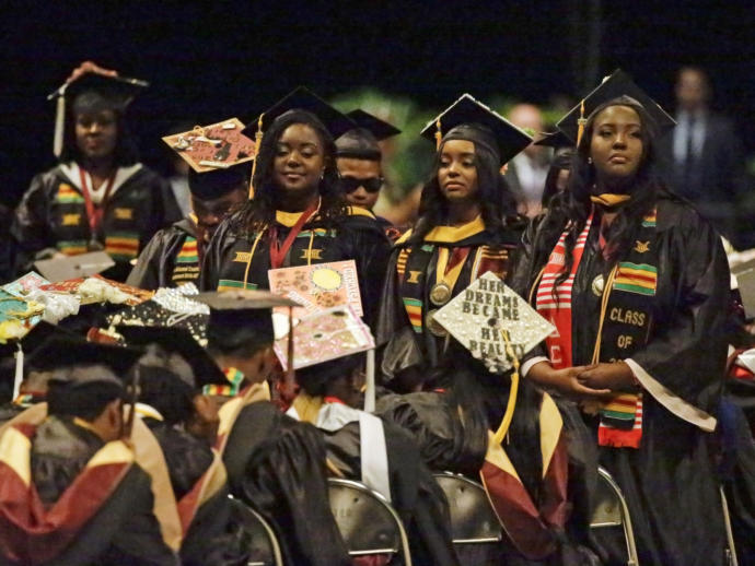 A group of students stand with their backs turned to DeVos during Wednesday's commencement speech.