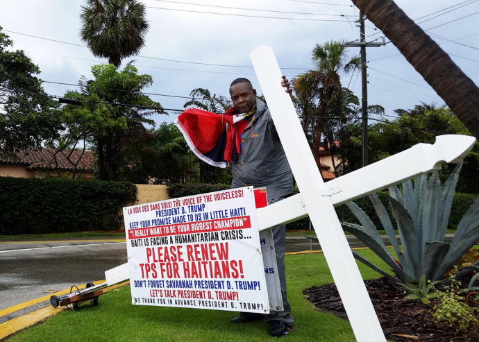 A protester stands in front of Mar-a-Lago, in Palm Beach, urging President Trump to extend the temporary protected status the federal government has offered about fifty thousand Haitian immigrants.