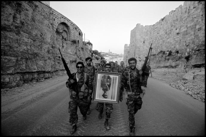Israeli soldiers, who recaptured the Old City from the Jordanians during the Six-Day War, carry a confiscated portrait of Jordan's King Hussein through East Jerusalem, June, 1967.